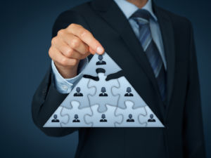CEO leadership and corporate hierarchy concept - recruiter complete team represented by puzzle in pyramid scheme by one leader person (CEO).