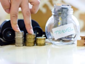 Travel budget - vacation money savings in a glass jar on world map. Collecting money for travel. Fingers stepping on the money.
