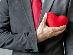 Businessman showing compassion holding red heart onto his chest in his suit - crm service mind business concept.